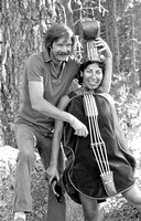 Michael Dixon plucking the strings of Christine de Herrera, Strawberry Bluegrass Festival, 1982, Leland Meadows